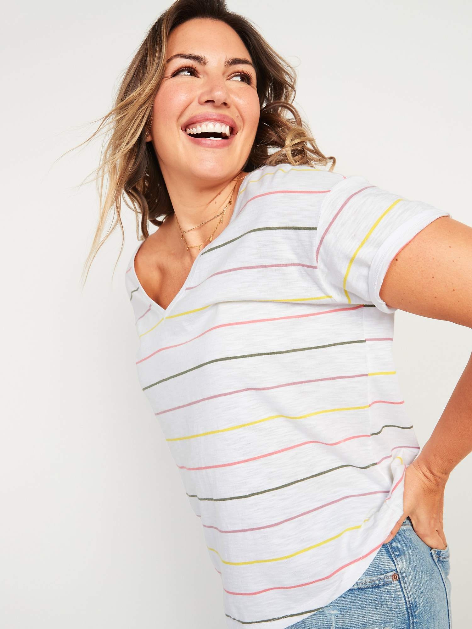 a woman wearing a white shirt with pink and yellow stripes